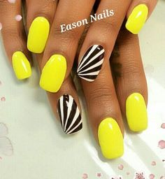 Beautiful yellow, black and white nail art design. The black and white polishes are used to create a diagonal effect on the nails while the rest of the nails are coated in matte yellow to give more attention to the black and white diagonal stripes.