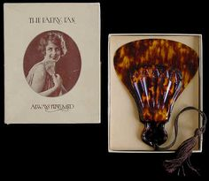 """The """"Faery Fan"""" is a 6 ½"""" long hand held celluloid fan that perfumed the air when fanned. It was patented in the in 1920 in the United States. The instructions say to insert a few drops of your choice perfume in a small round hole neat the upper handle. The constant flow of air, when the fan is in motion, will create a pleasing result. A price sticker on the fan indicates it was purchased for 75¢ from the J.W... Robinson & Co. that is now Robinson May, a California based department store."""