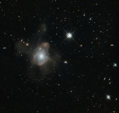 Galaxy undergoing a galactic merger, leaving a fine mist, made of millions of stars spewing from it in long trails