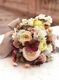 "The bridesmaids bouquets will be a clutch of ivory garden roses, burgundy anemoens, light pink ranunculus, ""butterscotch"" roses, burgundy tulips, white sweetpeas, gold seeded eucalyptus, burgundy scabiosa, grey dusty miller, and burgundy spray roses wrapped in raffia with the stems showing."