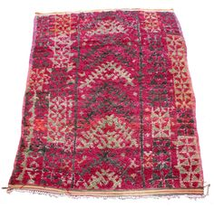 The thick high pile on this vintage rug softens the motifs, and is woven in deep magenta, sage green, charcoal and apricot. The Berber motifs create a sense of movement from one end of the rug to the other, bringing together numerous symbols in a harmonious whole. This heavy rug is in lovely condition www.maroctribal.com