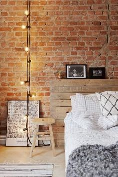 25 gorgeous bedroom decorating ideas - exposed brick walls, wooden headboard, mixed with diamond + grid pattern pillows, a modern wooden stool as a nightstand, string lights + gray shaggy throw
