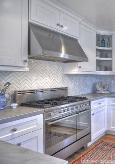 The zinc countertops are so chic and modern! They go so well with the stainless steel kitchen hardware and hood.