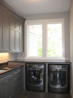 Contemporary laundry room features gray cabinets painted Benjamin Moore Cos Cob Stonewall paired with black quartz countertops. A gray laundry room wall painted Benjamin Moore Sleigh Bells lined with an enclosed washer and dryer placed below windows. Laundry Room Remodel, Laundry Room Cabinets, Laundry Room Organization, Grey Cabinets, Kitchen Remodel, Clean Cabinets, Laundry Organizer, Cherry Cabinets, Laundry Storage