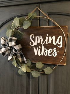 "Welcome Spring with this door hanger thats a little bit farmhouse, a little bit mod. It features a rich brown stained sign saying Spring Vibes"" with a gold metal circle accent and cute greenery and buffalo plaid bow. Jute twine for hanging. * wood sign measures approx 15"" x 9"" Total from top of"
