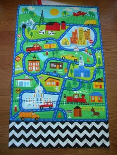 This large quilted play mat of a town scene will provide hours of fun for any special little boy or girl! This car play mat with roads and