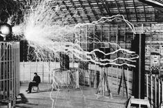Nikola Tesla in his lab, casually reading while volts of electricity fly through the air, 1899