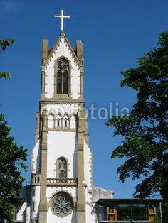 Kirchturm mit großem Kreuz vor blauem Himmel in Frankfurt am Main