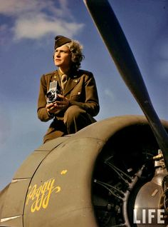 Portrait of LIFE photographer and journalist Margaret Bourke-White (1904 - 1971), dressed in an airforce uniform, as she sits atop the engine (labelled 'Peggy') of a B-17 bomber named 'Flying Flit-Gun,' Polebrook, Northamptonshire, England, fall 1942. The plane originates from the 97th Bombardment Group of the 8th Bomber Command (later 8th Air Force) which was stationed at Polebrook from June until November of 1942. (Photo by Margaret Bourke-White/Time  Life Pictures/Getty Images)