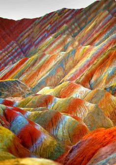 Zhangye Danxia Landform Geological Park in China. Layers of different colored sandstone and minerals were pressed together over 24 million years and then buckled up by tectonic plates, leaving a breathtakingly colorful mountainscape. #WorldBeautifulPlaces #Mountains