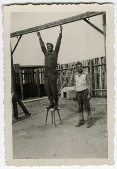 """An American soldier and a survivor show the gallows at Buchenwald. The inscription on the back of the photograph reads, """"Here's where they hang them at Buchenwald Concentration Camp. Ropes gone."""""""