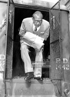 Frank Costello just released from Federal Prison steps down from police van outside the Charles Street station house. He just finished a stretch for income tax evasion.