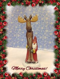 Hand carved Santa peeking out from underneath moose by Susan M. Smith