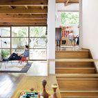 The exposed wooden rafters and grid of windows in the living room are original to the house.  Photo by Daniel Hennessy.