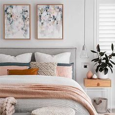 A stylish bedroom with a double bed, twin art paintings over the gray headboard, layered throw pillows on top of the bed including pink ones, as well as a pink throw at the bottom end of the bed.