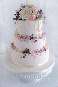 3 tier wedding cake with handmae sugar blossoms and sugar flower bouquet on top.