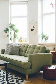 Green sofa…black and white rug, off white walls, no curtains…feels light and bright…the color scheme = black and white with olive accent…maybe you need to simplify your color scheme?!?