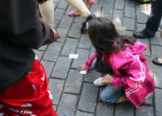 A child picking up cards from the russ in the street (2011 in Oslo).