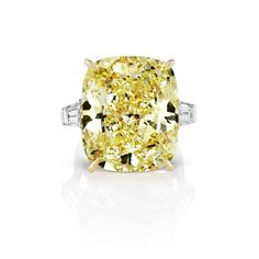 Fancy vivid yellow cushsion cut three stone engagement ring with baguette side stones | Scarselli DIamonds