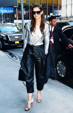 Katie Holmes looks chic in a metallic sweater, leather pants, t-strap heels, and square sunglasses