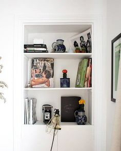 built-in shelves displaying books, ceramics and vintage camera and light. / sfgirlbybay