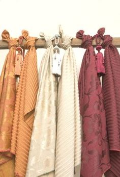 Kestrel Lister -  Hampshire Fabric Collection - Lustrous patterns and stripes on six swathes of fabric tied to a pole: two in orange, two in ivory, and two in aubergine