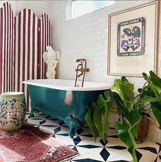 Boho bathroom decor inspiration - add a screen for added privacy in front of a bathroom window. This bathroom is all about the details - the wall art, plant and painted clawfoot tub all work together.