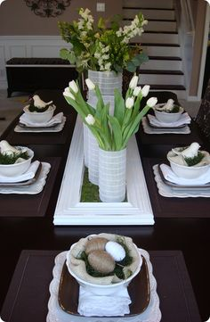 Spring Tablescape: Faux moss blanket in a white shutter (?), Yarn & string wrapped plastic eggs, set in bowls lined with burlap & more moss. Lots of fresh white flowers.
