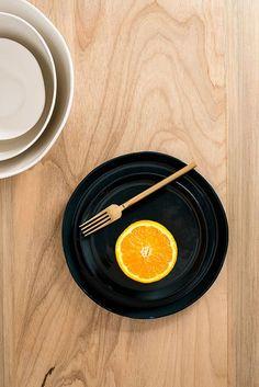 Prato negro com garfo dourado e tangerina cortada. Peças criadas por Carolina Zamboni Peraça