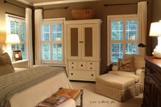 Savvy Southern Style: Home Tour -- drapery rods, drapes on one side, chair with ottoman