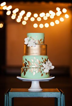 Brides.com: . A four-tiered mint-and-gold wedding cake with gold-leaf details and fresh flowers, from Artisan Cake Company.