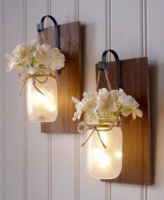 This Hanging Mason Jar Sconce has a natural look that spruces up any room. It comes with faux hydrangeas that are removable. The inside of the jar is filled wit jar Crafts Hanging Mason Jar Sconce Mason Jar Sconce, Hanging Mason Jars, Mason Jar Lighting, Painted Mason Jars, Jar Lamp, Diy Mason Jar Lights, Jar With Lights, Mason Jar Painting, Mason Jar Lanterns
