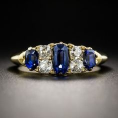 A ravishing and radiant rarity! From turn-of-the-last-century Great Britain, a classic carved ring hand fabricated in rich 18K yellow gold starring centerstage: a gorgeous royal blue faceted elongated oval sapphire weighing a modest three-quarter-carat, accompanied by gemological report from Stone Group Laboratory stating: No Indications of Thermal Enhancement, Burma origin! (And one may reasonably assume that the small matching pair are the same.)