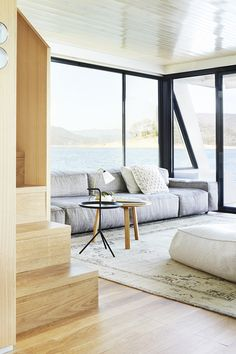 Neutral houseboat living room with light wood accents and large windows