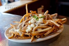 Poutine - Canadian french fry dish covered with fresh cheese curds and gravy