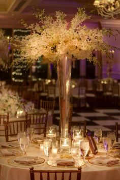 Some of the centerpieces will be tall trumpet vases mounted with a large spray of white hydrangeas, blush pink roses, blush pink stock flowers, and blush pink dendrobium orchids surrounded at the base by skinny cylinders with floating candles and mercury glass votives.