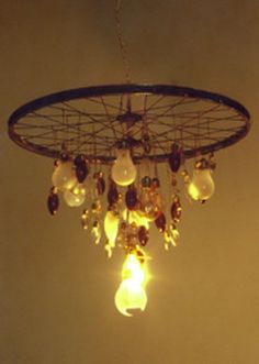 Hang lightbulbs on an old wheel and voila! You have a chandelier.  There is something about this that appeals to me....but it needs somthing...i'll figure it out...because i think i need this.