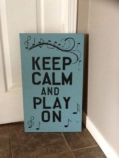 Keep calm and play on wood sign.