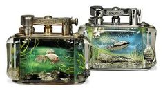 Image issue du site Web http://www.christies.com/lotfinderimages/d53701/two_aquarium_table-lighters_by_dunhill_20th_century_d5370161h.jpg