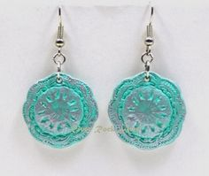 """These ceramic earrings have a vintage-style design with an aqua base color and metallic silver antiquing on both sides of the earrings. They are finished with a glossy sealer. The earrings measures 7/8"""" (2.2 cm) in diameter.  From the top of the hook to the bottom of the earring is about 1 1/2"""" (3.81 cm).  You can find the matching pendant here:http://www.zibbet.com/RiverRockArts/artwork"""
