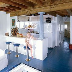 Retro bar stools and blue painted floors add a whimsical touch to this beach cottage kitchen.