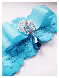 handmade blue wedding garter with lace, pearls, bow, feathers and swarovski crystals, source: www.vertigo.com.pl