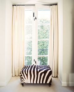 Hollywood Regency Furniture Photo - A zebra-covered ottoman in front of French doors with white curtains