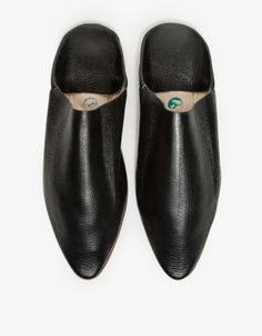 Moroccan inspired leather Babouche slippers in black. Features slip on style, pointed toes, padded footbed, stiff mahogany tone outsole and matching black stitching.  • Babouche slippers in black • Leather material • Padded insole • Stiff mahogany to