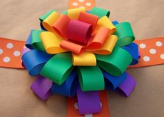 How to make construction paper and recycled paper BOWS at http://www.olderandwisor.com/2012/01/how-to-make-loopy-paper-flower-bow-gift.html