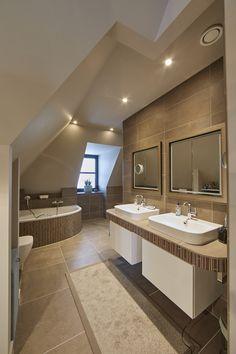 In deze bruine badkamer is de combinatie gemaakt tussen grote en kleine tegels. De bruine tinten zorgen voor een rustgevende sfeer. Het grote ligbad is perfect voor ontspanning.