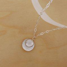 Silver necklace with a textured silver circle cradling a smaller silver circle