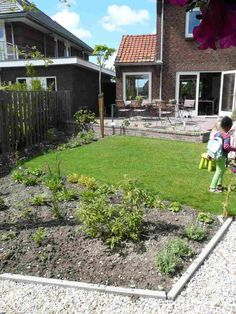 Nieuw aangelgd tuin met schuine lijnen en verhoogd teras.