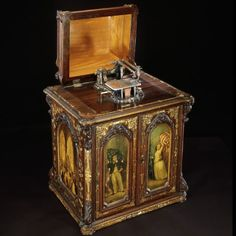 A full-length photo of the sewing machine. It looks like a box with painted doors featuring images of a man and woman. The top is open to show the sewing needle. Korean Drama Online, Wizard Of Oz 1939, Double Headed Eagle, Dancing Dolls, Princess Stephanie, Painted Doors, Bobbin Lace, Floral Motif, Rose Buds