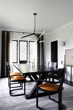 The design of the dining room began with a custom color version of Brian Paquette's new wallpaper called Nantes from Studio Four NYC. The team played off the leaded windows with custom wall sconces by Jason Koharik. In addition, ombre drapes by Zak+Fox, chairs by Nickey Kehoe, and a chandelier by Lindsey Adelman balance the modern sensibilites of the client with the history of the home.